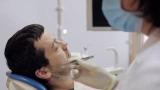 The dentist puts a cotton ball near the patient's tooth.
