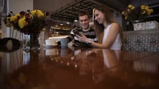 Two young caucasian people watching a smartphone in a cafe and laughing