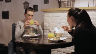 Two young women eating and talking in a cafe