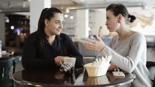 Two young women sitting and talking in cafe.