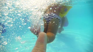 Underwater shot of baby girl swimming in the pool