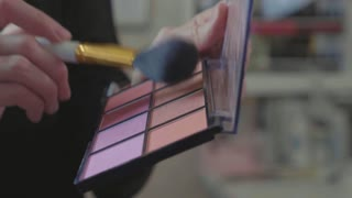 A palette with eye shadows and a makeup brush: women's cosmetics.
