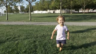 An adorable little girl runs toward the camera with a large smile on her face.