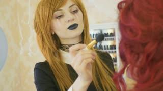 Artist with halloween makeup applying halloween makeup on model's face.