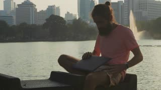 Bearded man opening laptop and start work on the bench at megapolis city park