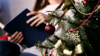 Beautiful young lady sitting on a chair near Christmas tree and reading a book.