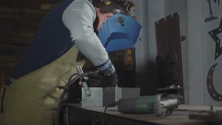 Blacksmith welding steel and iron in slow motion at his workshop, close-up.