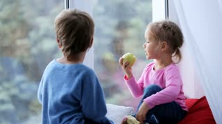 Brother and sister sits on window sill, eating apples and looking out window.