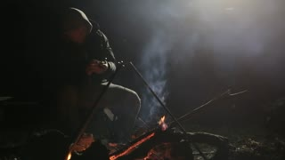 Caucasian man sitting next to bonfire and using smart phone at night.