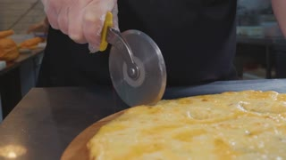 Chef cutting hot ready pizza by rolling pizza cutter, close-up slow motion