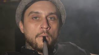 Close-up portrait of men smoking a hookah and exhaling lot a smoke at camera