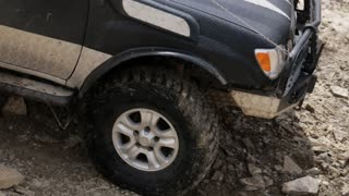 Close-up video of exprditionary SUV slowly rides on the mountain rocky road.