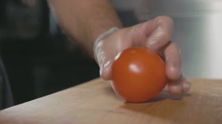 Closeup chef hands cutting slices of tomato on wood cutting board