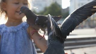 Closeup portreit of little cute girl feeding street pigeons in the park
