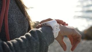 Closeup woman using smart sport running watch on the beach