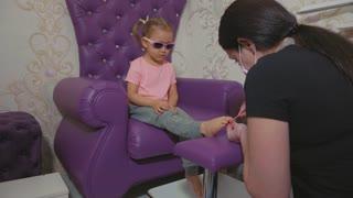 Cute baby girl at pedicure procedure in beauty spa salon.