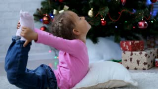 Cute little girl doing yoga exercise on the floor next to Christmas tree