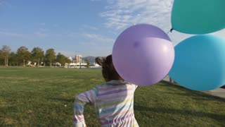 Cute little girl running with balloons in the park and laughing