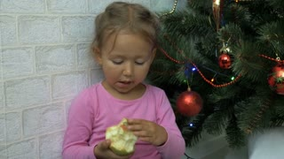 Cute little girl sitting on the floor and eating apple next to a Christmas tree.