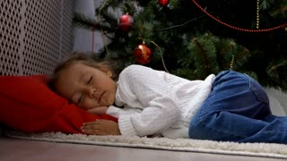 Cute little girl sleeping under Christmas tree at morning