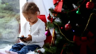 Decorated Christmass tree and little girl with smart phone on the background.