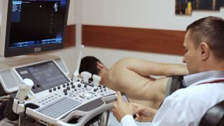Doctor clicks smart phone while patient lying and waiting ultrasound diagnostic