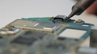 Electronics repair soldering microchips and circuit boards