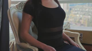 Elegant young woman in black dress relaxing on chair near window at hotel lounge