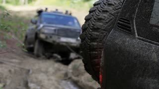 Expeditionary SUV got stuck in the mud in the forest and get out via another SUV