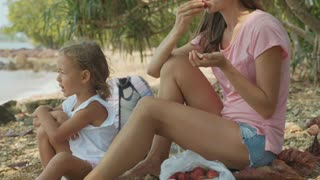 Family sits on a tropical beach and eats fruits in slow motion.