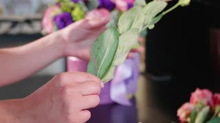 Florist girl makes a floral box in a flower salon, close-up