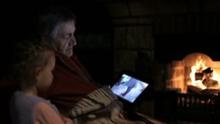 Grandfather with granddaughter watching video in tablet at the fireplace