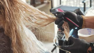 Hairdresser is untangles the hair of blond female customer at beauty spa salon