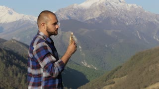 Handsome bald hiker, in nature eats a bread at beautiful mountain landscape.