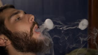 Handsome young guy smoking hookah and makes rings of smoke.