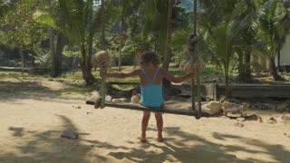 Happy child girl swinging at tropical sandy beach