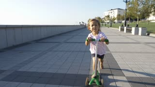 Happy cute little girl riding kick scooter in the park at sunny summer day