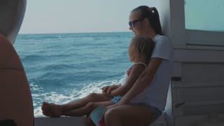 Happy family of mother and little cute daughter trip on the boat in slow motion