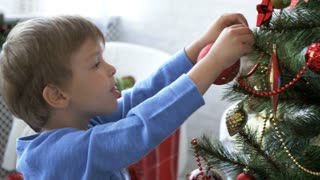 Kids decorating Christmas tree in light room at daytime