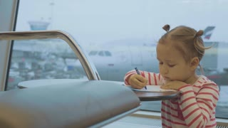 Little baby girl drawing at airport with plane on the background