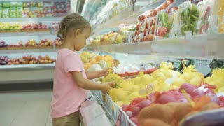 Little cute child girl choosing vegetables in grocery store