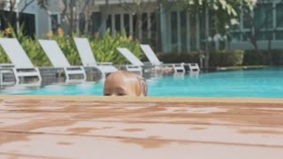 Little cute girl climbs out of the swimming pool, in slow motion.