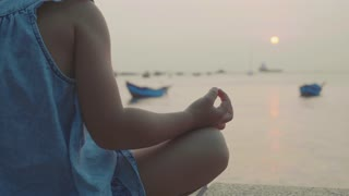 Little cute girl meditates in turkish pose at seafront
