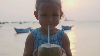 Little girl drinks coconut water at seafront on sunset in slow motion.