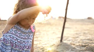 Little girl holding sand in hand on a beach and letting it fall down again.