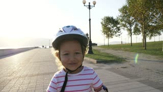 Little girl in helmet and protection riding on roller skates in summer park