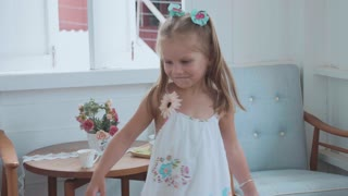 Little girl in white dress is spinning at home in slow motion