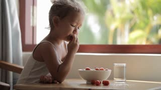 Little girl sits by the table and eating cherry tomato