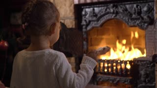 Little girl throwing woods in the flame of fireplace