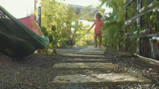 Little girl walking on path in garden. Close-up feet come near to camera.